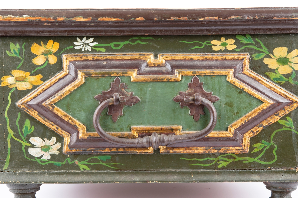 Sinket treskrin med dreide ben, ett ben ulikt. Smidde håndtak, nøkkelskilt, lås og hengsler. Rosemalt dekor. med skjell, blomster og akantusranker. Forkrøppede speil på sidene og lokk.
