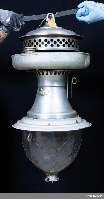 """Grupp I:IV.  Autoluxlampa för 500 normalljus (nlj) i låda. På lockets insida är inskrivet med blyerts """"No 13123"""". Kistan innehåller 1 st spritmått, 4 (?) kartonger med glödnät, 1 stålborste och en obruten förpackning med reservdelar (2 stift, 1 galler, 1 handrensnål, 1 munstycke, 1 par munstycksnycklar, 1 mutternyckel, 1 fyrkantsnyckel)."""