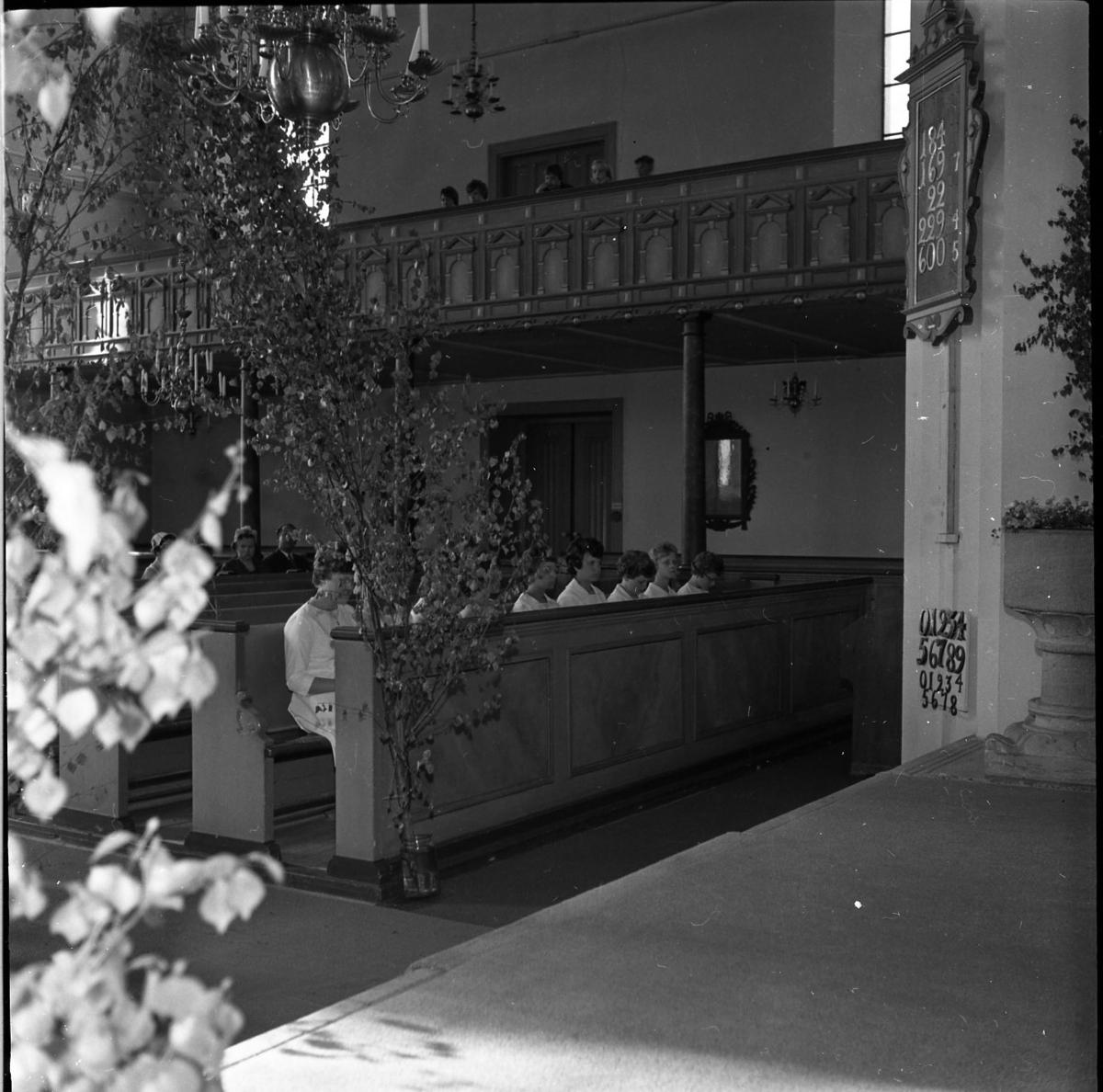 Interiör från Gränna kyrka i samband med konfirmation. Kvinnliga konfirmander sitter i en bänkrad längst fram.