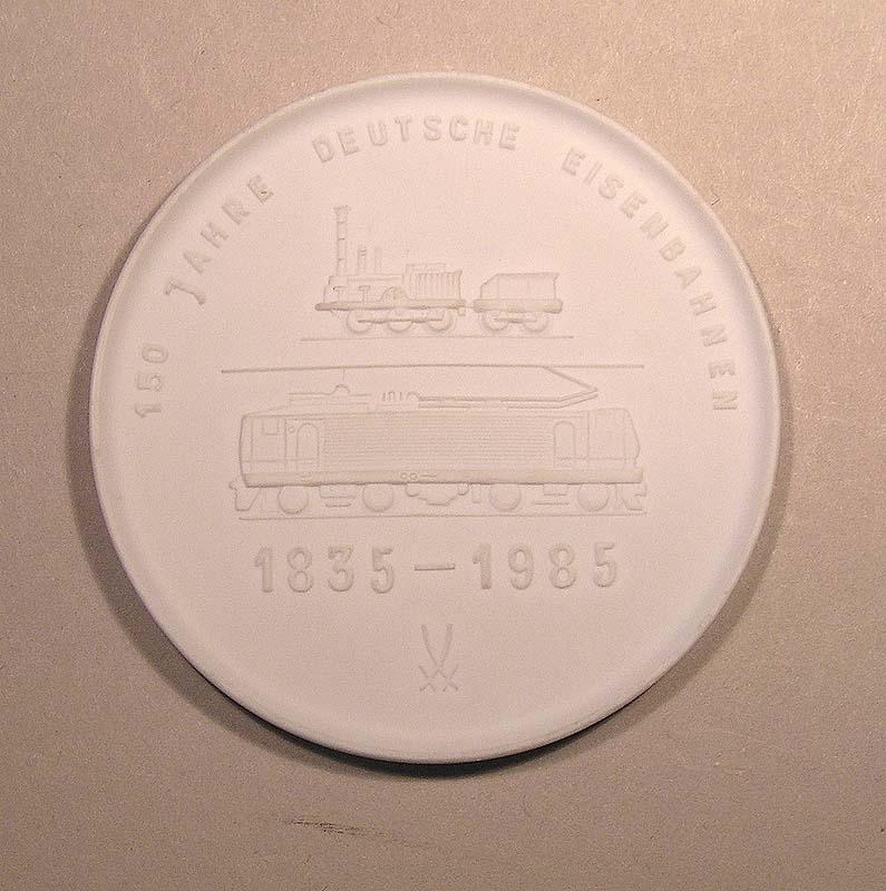 """Minnesmedalj eller plakett av vitt porslin från Tyska Järnvägen 150 År 1835-1985. Text på ena sidan: """"40 Jahre Eisenbahn in Volkes Hand"""". På andra sidan: """"150 Jahre Deutsche Eisenbahnen""""."""