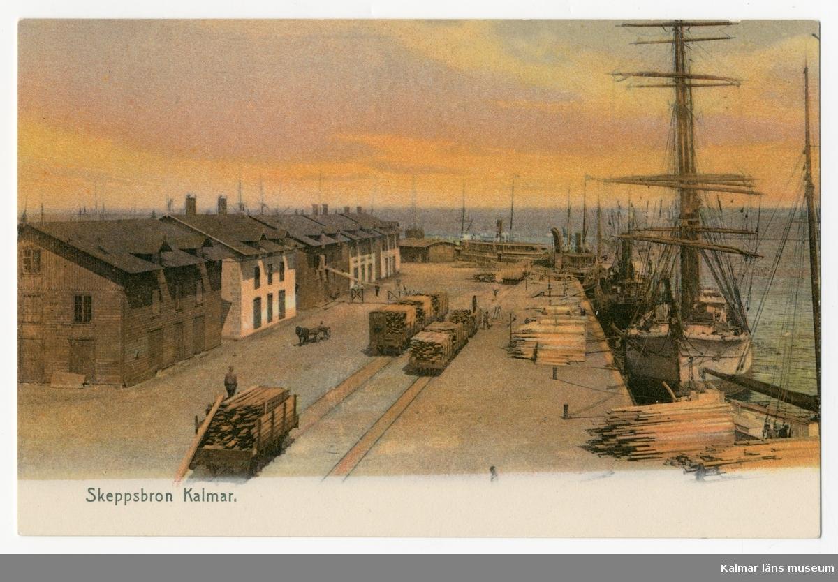 KLM 46453. Vykort, av papper. Tryckt motiv med skepp som lastas med virke vid Skeppsbron i Kalmar. Text under motivet: Skeppsbron Kalmar.