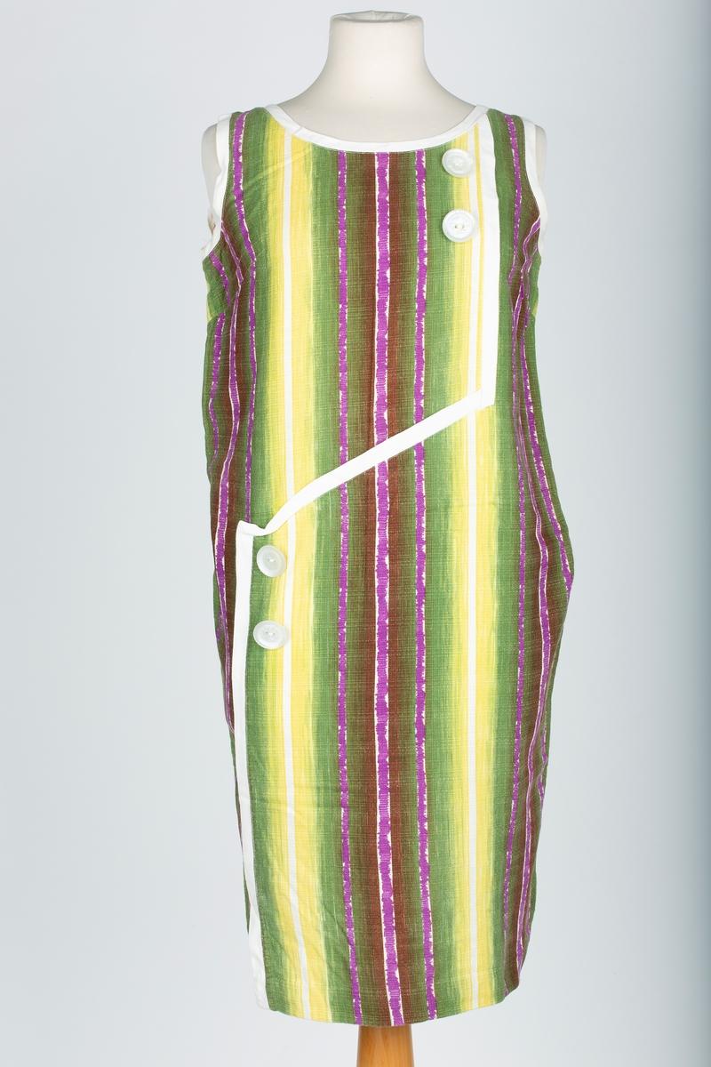 Sommerkjole. Rette sider. Brystsnitt. Uten ermer. Forstykket satt sammen av to stoffbiter sånn at det blir en skråskjøt og en langsgående skjøt. Oval hals. Hals- og armringing og skjøtesømmer på forstykket kantet med hvitt skråbånd. Kanting med skråbånd.  4 store hvite pynteknapper på forstykket.  Laget av stoffrester som opprinnelig var brukt til russeløyer. 5m stoff ble til 3 kjoler Kjolen sydd av mor.