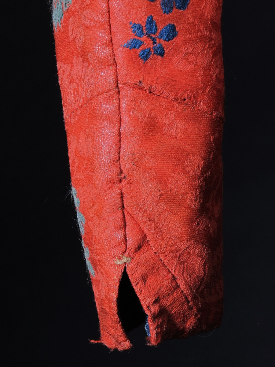 Brudetrøye (overdel til kjole),  Rød  damaskvevet lin med ull  blomsterbroderi  i blått, mørkt- og lyst-grønt og gult,   (nelliker og små strøblomster).   Innsvinget i livet, rekt. halsåpning, ermene vide ved   skuldrene, smalner nedover.  Ryggen  figurskåret, ansats til kø. Foret med blått grovt  strieliknende stoff, renninggrå lin i slett blå ull.  foret restaurert? Med beige strie  nederst.