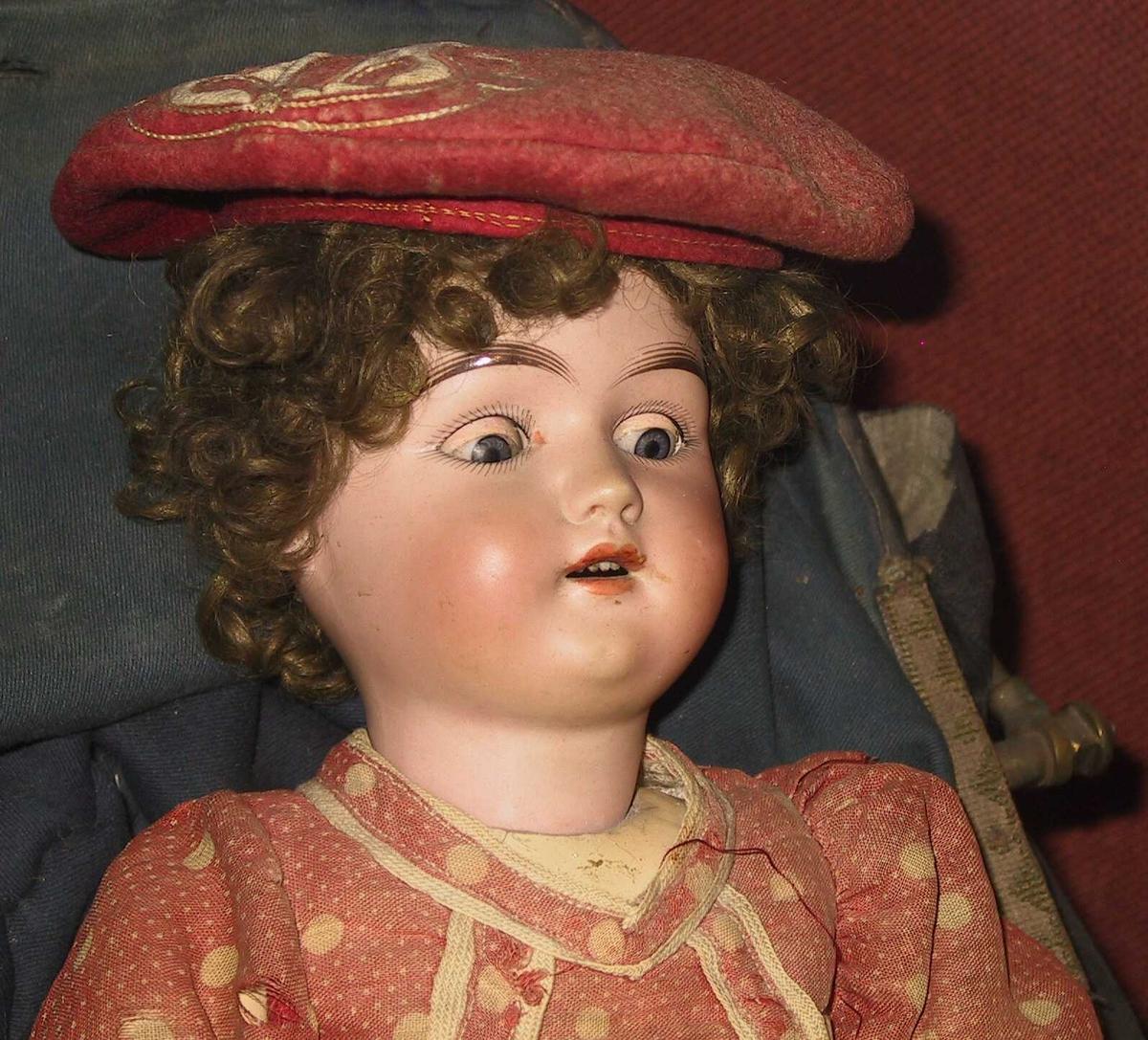 Dukke, påkledd, fra  beg.  av 1900 tallet.     Porselenshode, leddet   tre  kropp.    Brunkrøllet hode, ekte hår, rose  karnasjon, blå  øyne som kan lukkes, åpen munn.  Armene har ledd  i skulder, albu og håndledd,  benene i knærne.  Tilstand: slitt, men i orden.    b) Kjole, hvitprikket rød   bomull, baklukket,  høyt liv med oversydde bånd, kantebånd nede.  falmet, særlig på forsiden.    c) Underskjørt, gulnet, med smal blondekant nede,  knyttet med strikk i ryggen.    d) Chemise, maskinstrikket tricot, hvit.    e-f) Strømper, som d), litt hullet og flekket.    g-h) Sorte sko med afikelrem, under sålen mrk. nr.: 3    i) Lue, rød, falmet, ull  med et ornament i siden