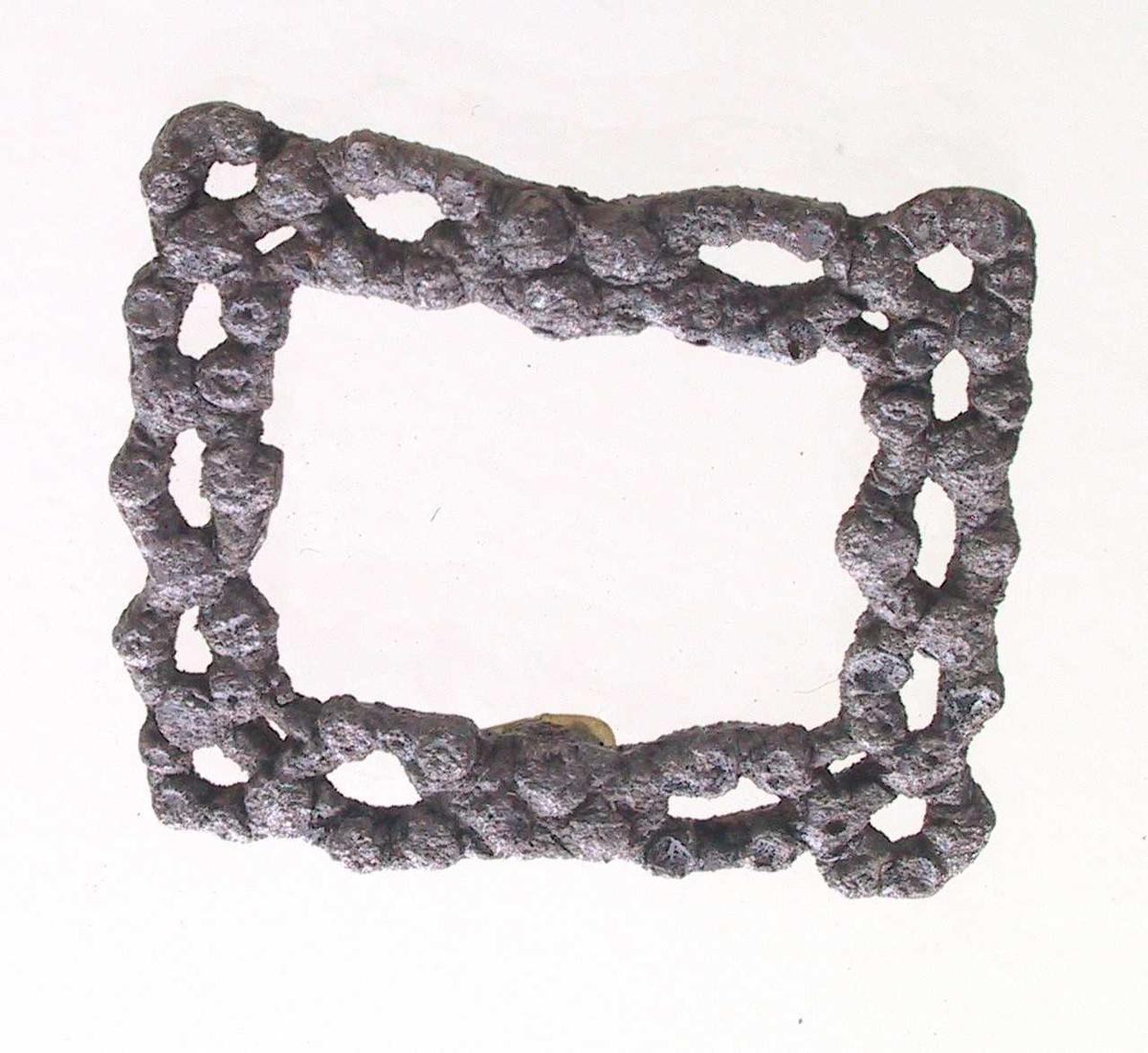 Knespenne støpt i metall, trolig bly.  Rektang. spenne i  gjennombrutt  ornamentikk: 2 slyngende  bånd  i ovaler som møtes pm. av hver langside i en  sløyfe.  Ovalen har små knapper,  som kan ha vært feste for små  bergkrystaller  eller glassperler.  Mangler hekte.