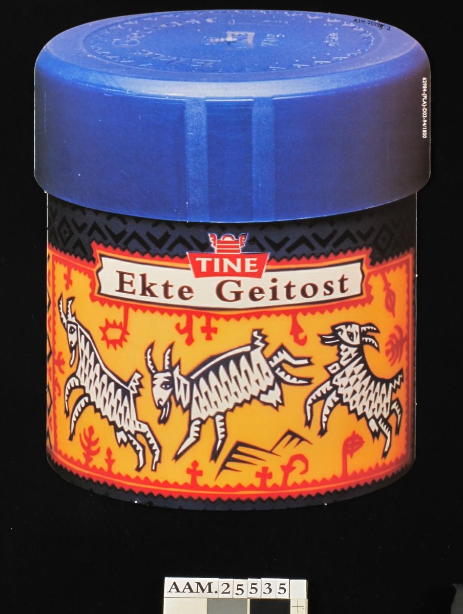 Fargefoto av rund ekte geitost. dekorert med tegnet motiv: Geiter innrammet i primstavmotiv.