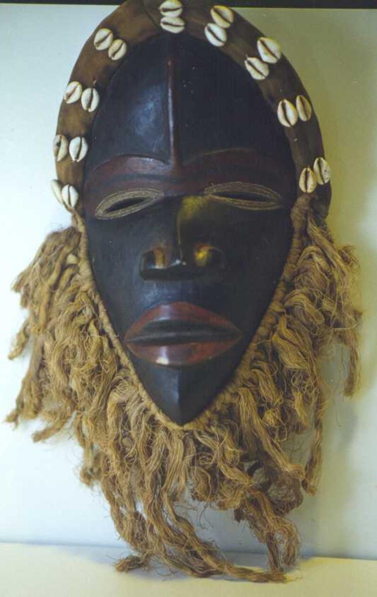 Maske, formet som et menneskeanskikt, m.lepper, nese, røde striper, skjegg, pannebånd m.skjell