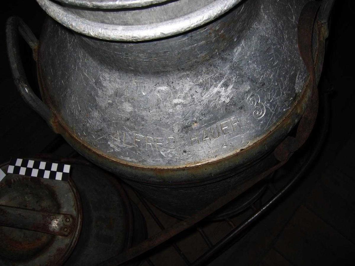 Melkespann i aluminium 50 L m. lokk. Hovedformen er trukket i aluminium. Fotring og ring med hanker er av galvanisert stål, og krympet på. Lokket er støpt i aluminium. Et lenkekefeste i støpt Al er klinket til spannet. Lokket er festet med lenke. I tillegg til gravert tekst, har spannet klistremerker i plast, røde tall på hvit bunn: 44 48