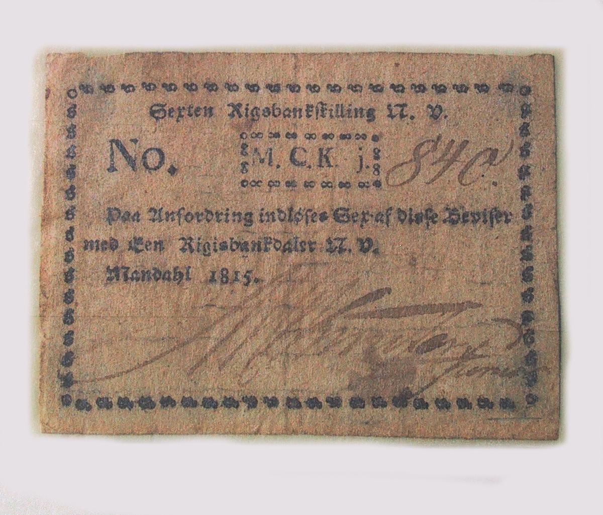 Til venstre loddret kartusj med JK&S . Til høyre heldende skrift. Nederst hvitt på sort:  48 SKL.