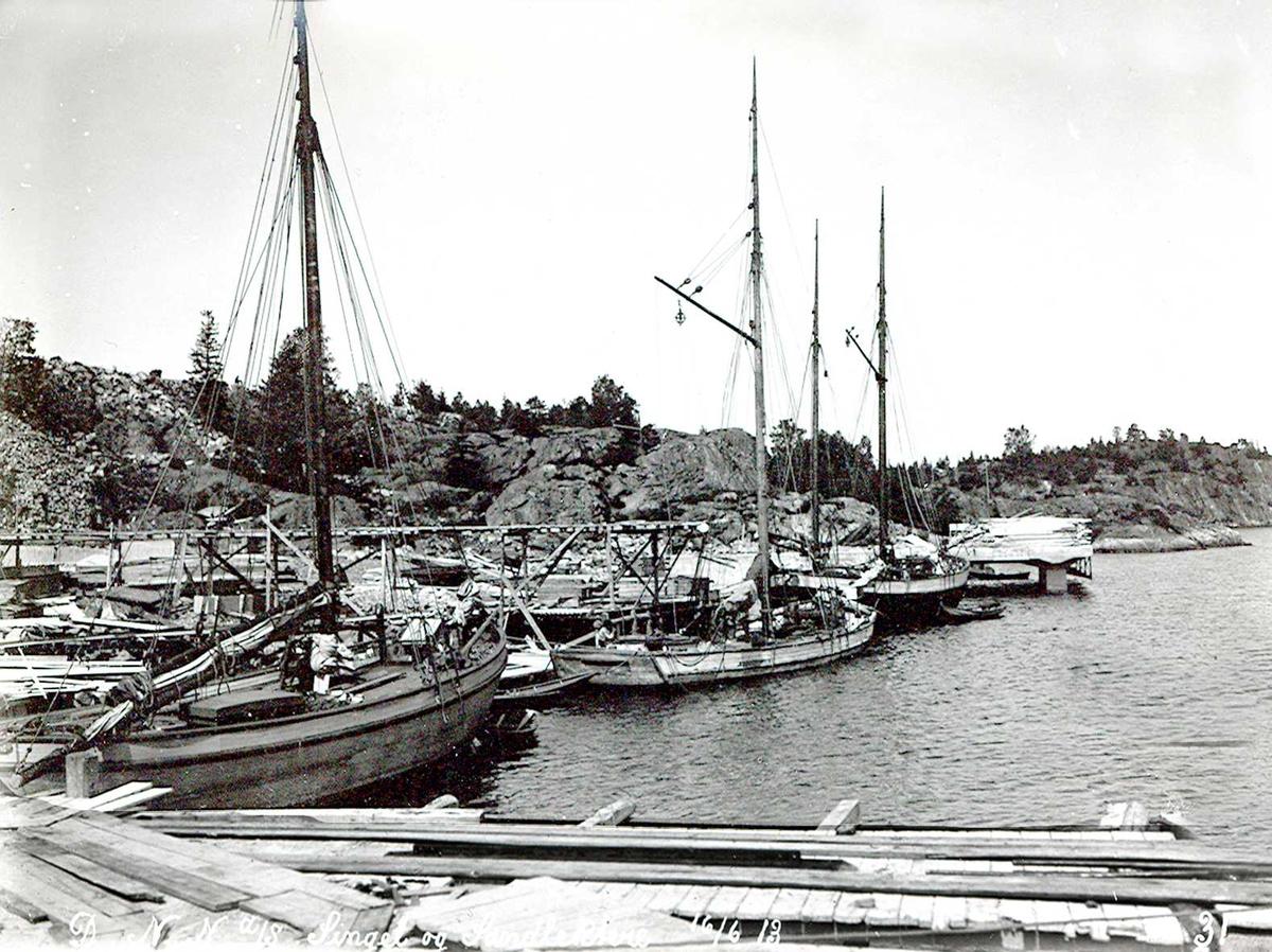 """""""16/06-1913"""" Nitriden. Tre frakteskuter på rekke og rad. Byggematerialer kom sjøveien."""