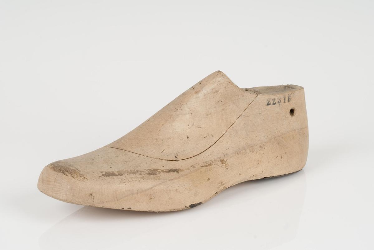 En tremodell i to deler; lest og overlest (kile). Venstrefot i skostørrelse 44, med 9 cm i vidde. Hælstykket av metall