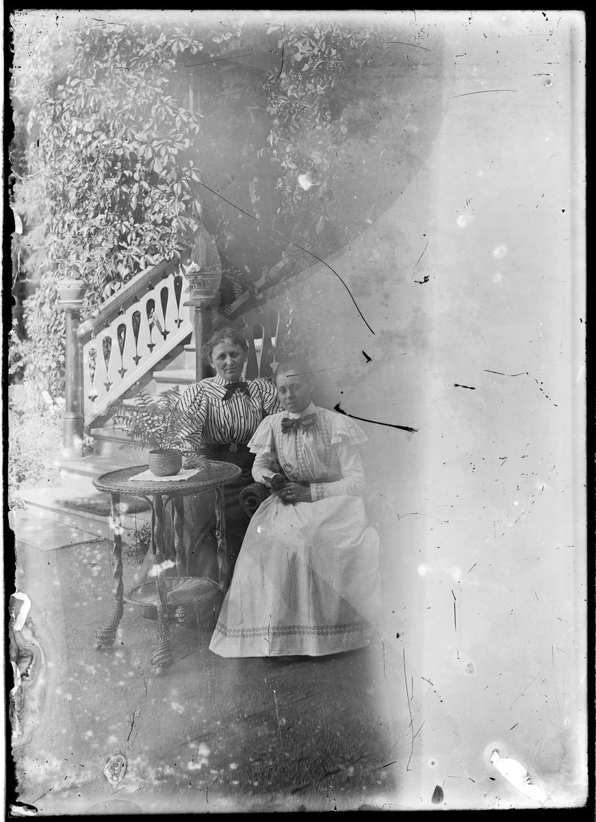 To damer som sitter ved et bord i hagen.