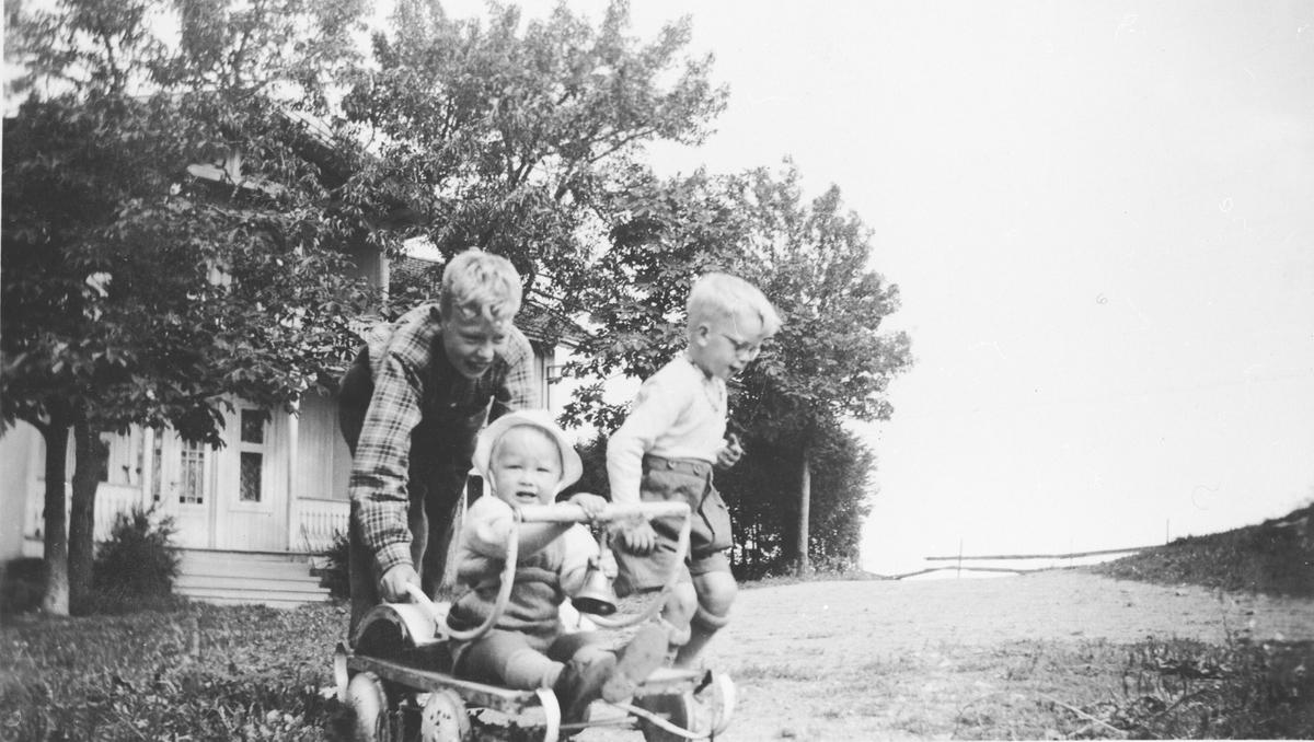 Barn leker med gammel barnevogn