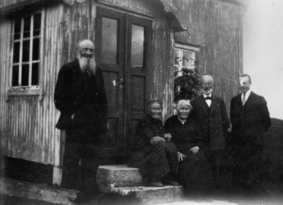 Eldre kvinner og menn utenfor hus.