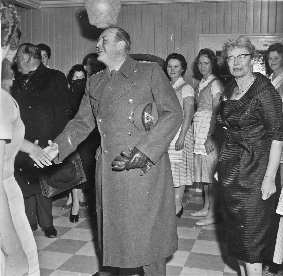 Etter åpningen av den nye Minnesundbrua 12. des. 1959 var det festmiddag på Akershus Fylkes Husmorskole. Her blir en smilende Kong Olav ønsket velkommen. Til høyre rektor Rønnaug Haga. Til venstre for Kong Olav Fylkesmann Trygve Lie.
