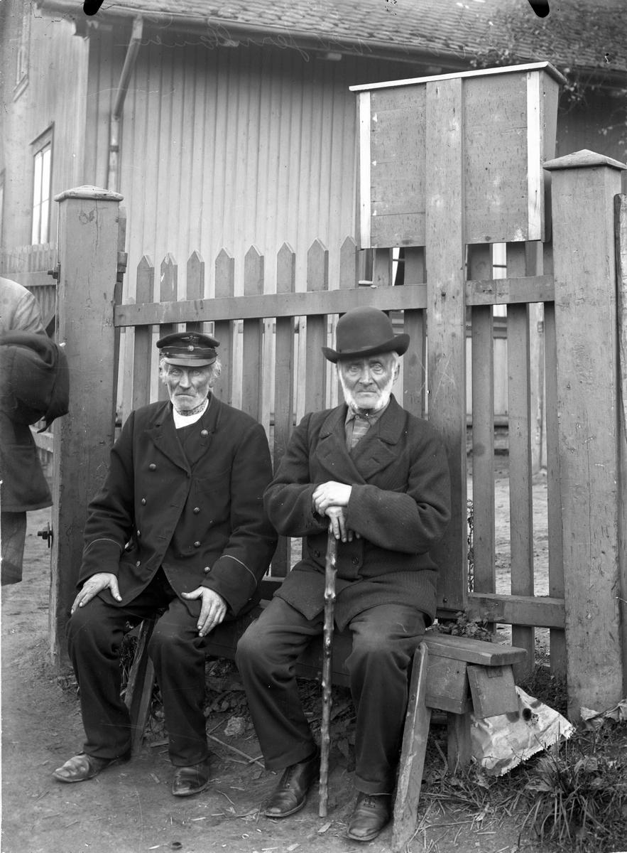"""2 gamle karer ved porten til Eidsvoll stasjon. Til venstre er den kjente Theodor """"ved porta"""". Til høyre pensjonert konduktør Adolf Hansen. Som billettkontrollør gikk han på utsiden av vognene og samlet inn billettene"""