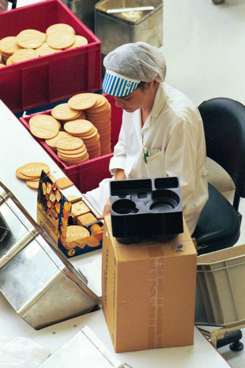 Håndpakking av kjeks, arbeidsmiljø, arbeider, kvinne, emballasje, fabrikkmiljø