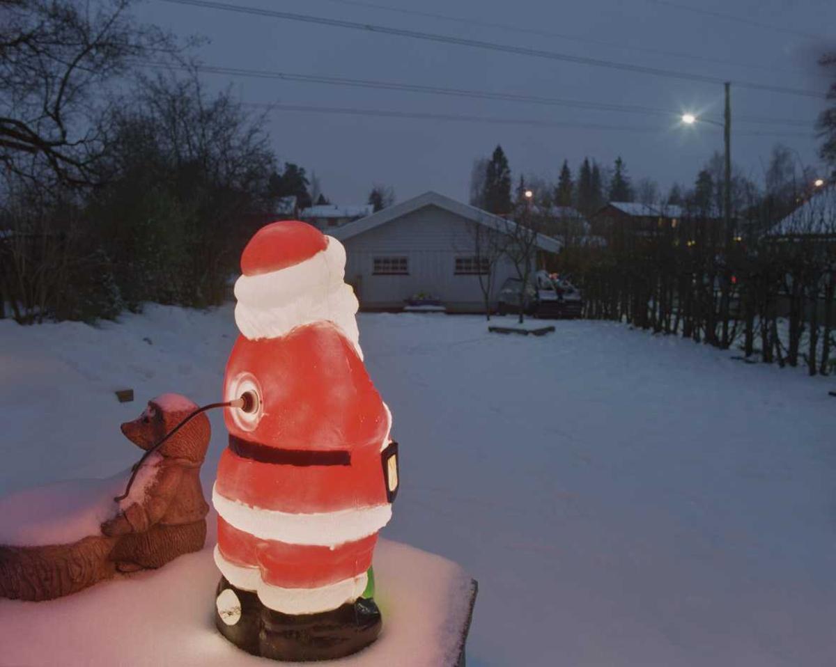 Julebelysning.    Lysende nisse står og ser ut på hagen ved rekkehus.