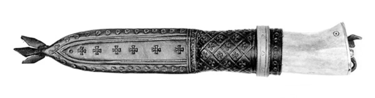 Kniven har skaft av reinsdyrhorn med skiver av never og svart bøffelhorn. Avslutningen mot bladet er av svart bøffelhorn. På toppen av skaftet er det plate av messing. Merket på begge sider av skaftet, O, er Henrik Vensilds bumerke. Slira er av svart lær, med hempe av brunt skinn. Slirefasong og dekor er middelalderinspirert. Slira er sydd direkte på kniven. Knivmakeren, Henrik Vensild ( ca 40 år 1980) laget kniven vinteren 1980.  Nummeret, 54, angir hvilken kniv det er i rekka av de han har laget. Han har vært mye i Norge, og har fått sin knivinteresse her.  Se også SJF 5842 og 5843.