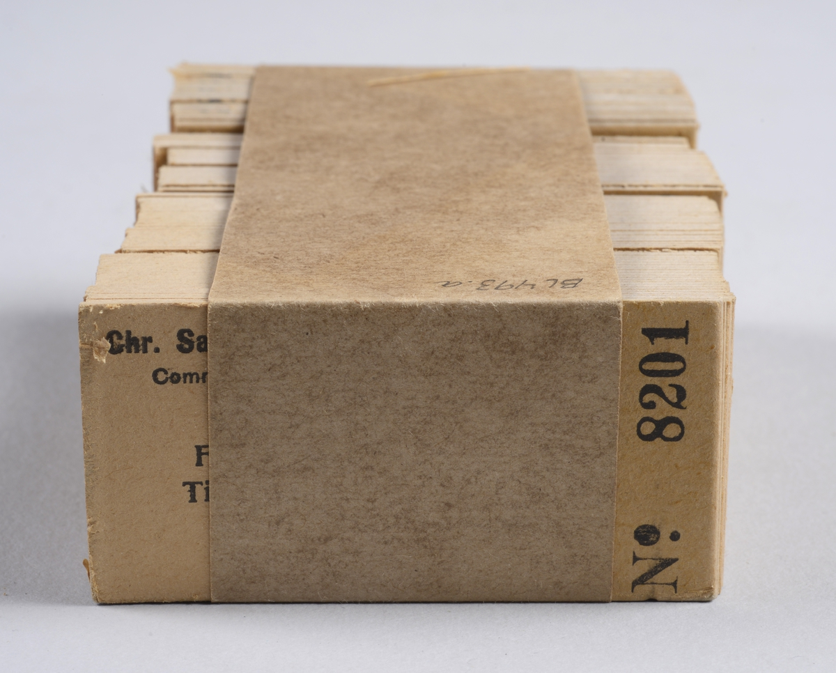 To bunker med rektangulære ubrukte togbilletter av papp med påtrykket informasjon. Billettene er holdt sammen med brunpapir på midten. Hver pakke inneholder 99 billetter, merket 8601-8700 og 8201-8300.