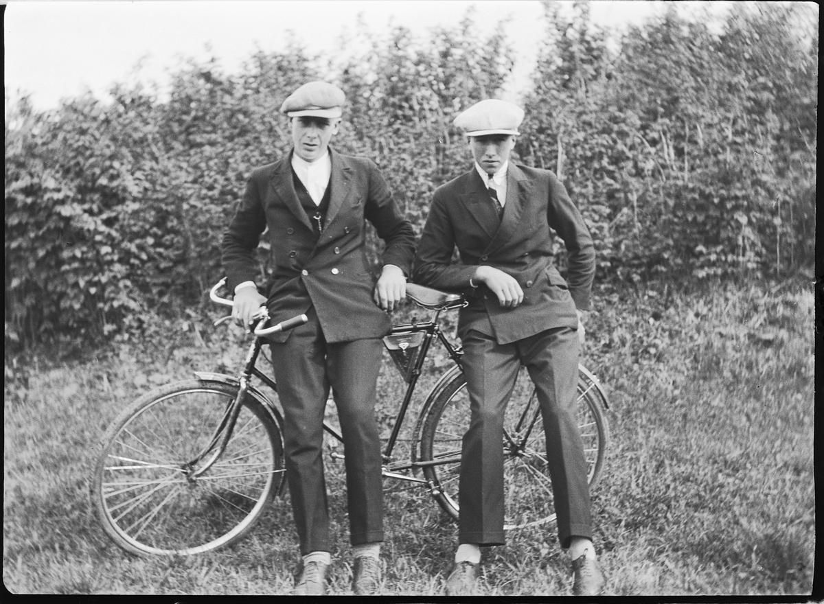 To menn støtter seg på en sykkel.