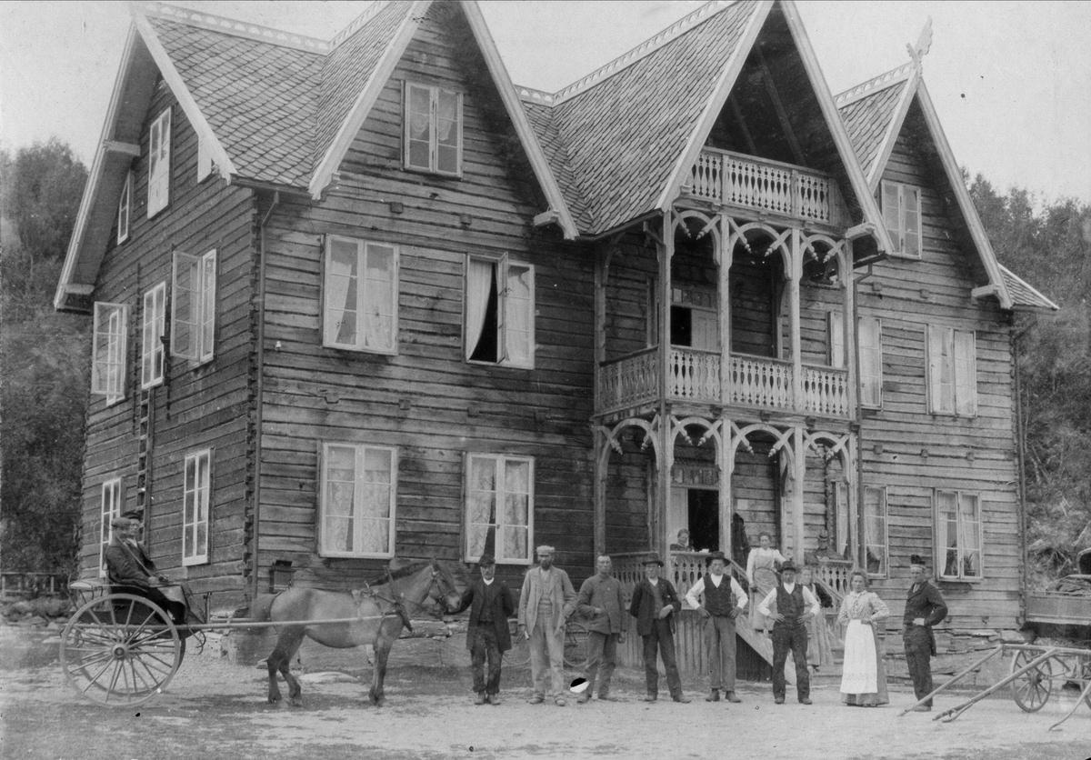 Villa i drage/sveitserstil med personer i forgrunnen.