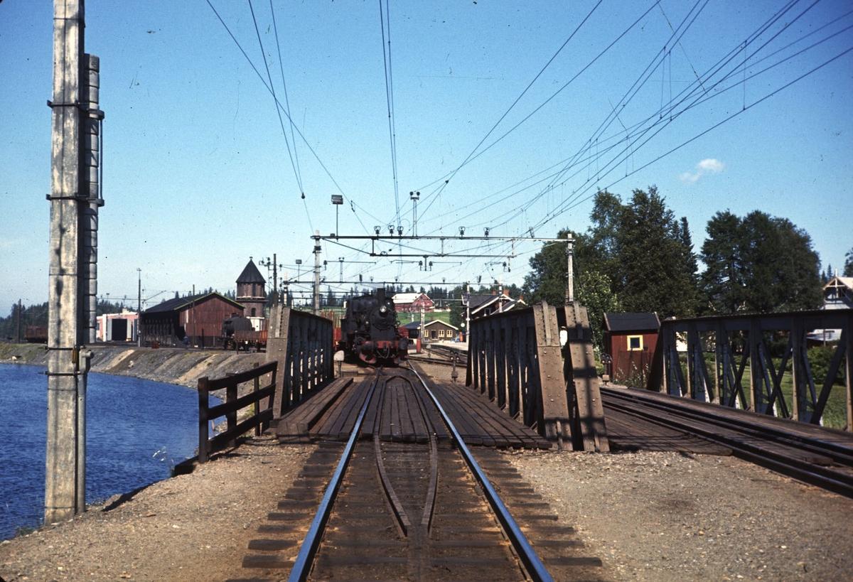 Skifting med damplokomotiv på Eina stasjon. Valdresbanen til venstre, Gjøvikbanen til høyre. Bro over Einavann i forgrunnen.