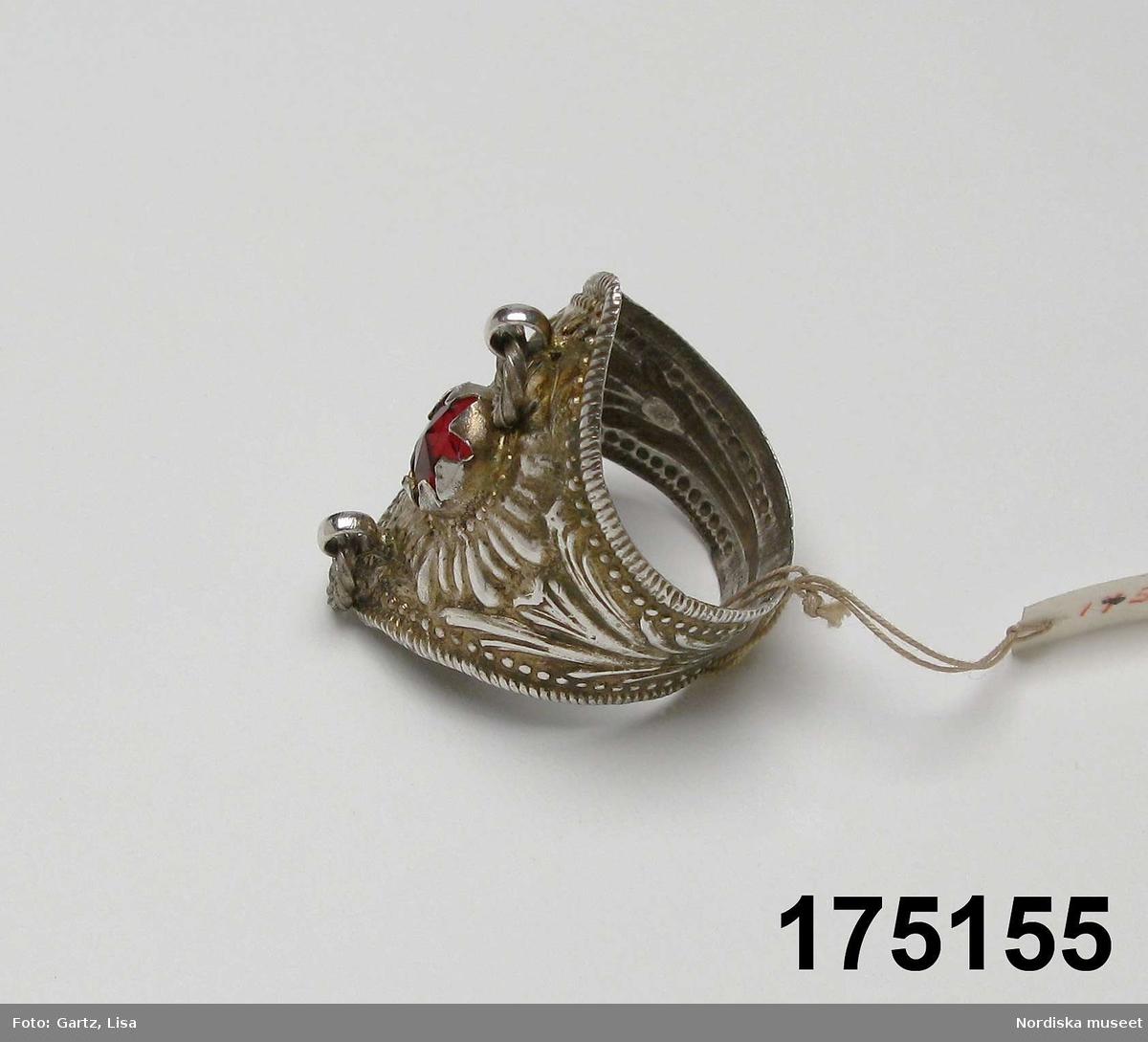 """Huvudliggaren: """"Fingerring av silfver, prässad med bred framsida med en röd glassten och 2 små hängande ringar. stämplad. N S."""""""