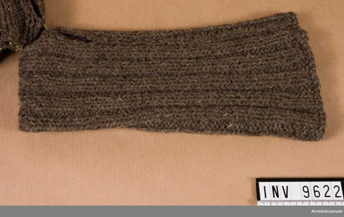 Mudd m/1944. Handstickad mudd i resårstickning. Ihopsydd på längden och med en kvarlämnad öppning 40 mm lång för tummen.  Samhörande nr är 9605-9650 + 9659-9666. I par 9621 - 9622.