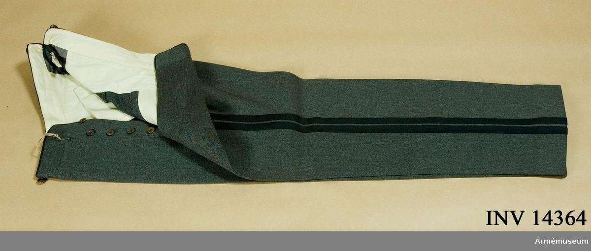 """Paraduniform m/1911 med gradbeteckning m/1923. Grupp C I. Av svart kläde. Två fickor på sidan och på baksidan spänntamp av kläde m spänne. På spänntampen firmans etikett av tyg """"H. C. Peterson & Hansen, Köbenhavn, Delningsforv. O Hansen, 449-29 (1929)"""". På byxans sida finns revär av två svarta silkesband, b: 13 mm. Foder av gult tyg. Svarta knappar, 5 st på sprund, 6 f hängslen. På byxans baksida två fickor m 2 knappar. Enl papperslapp från Töjhusmuseet tillhör byxan """"Kongens Livjaegerkorps, Officer, Gallauniform m/1911/1923, bukser"""".Enl Granberg 1951."""
