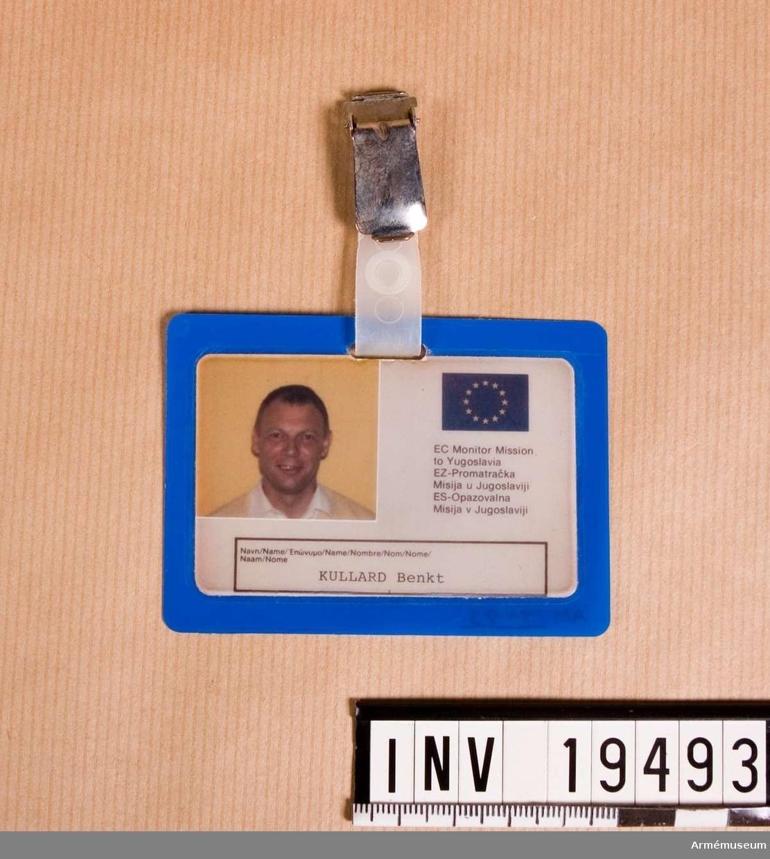 """Identitetsbricka i plast och med foto av Bengt Kullgard och EG:s symbol de 12 gula stjärnorna på blå botten och text: """"EC Monitor Mission to Yugoslavia"""" och denna text översatt till två språk till. På baksidan följande text """"Tillhör europakommisionen."""" Denna mening är översatt till 9 språk.  Ytterligare en mening finns att läsa: """"Den person som finner detta kort skall ge det till polisen."""" översatt till 9 språk. På baksidan är Kullgards blodgrupp angiven, dvs 0+.  Samhörande nr AM.19483-19494"""