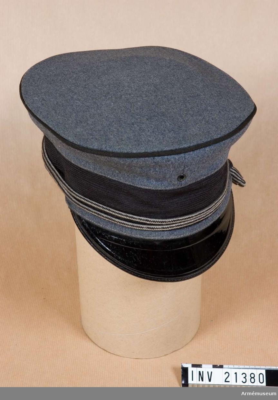 """Grupp C I. Ur uniform för kadett i West Point, USA. Består av frack, långbyxor, kappa, skärmmössa, tschakå med ståndare, tygfodral, vantar, livrem med spänne, fältmössa.  Buren av Richard A Gillespie. Av grått kläde med fastsydd svart band på bräm och mörkgrå passpoal i kullens övre kant. På mössans båda sidor finns två två luftventiler och framtill en. Foder av svart bomullstyg med stämpel """"Kadet W.M. Dept U.S.M.A"""" Svettrem av brunt läder med påskrift """"Dunjon"""". Skärm på framsidan av svart lackerat läder. Snören av grå-svart ylle med löpare och träknappar på ändarna. Mössan tillhör kadettuniform i början av detta sekel."""