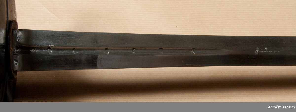 """Grupp D II.  Värja för kavalleriet. """"Karl XII:s tid"""" (1697-1718). Klingan är tveeggad med flata åsar. Upptill på var sida finns en blodrand, som på båda sidor är omkring 165 mm lång. I bottnen  på varje blodrand är 6 otydliga bokstäver, troligen COCOCO  anbringade och vid slutet på var och en av blodränderna finns  ett ornament av fyrkantiga prickar. Upptill på yttersidan finns  en skadad P-stämpel.Fästets metalldelar är av svärtat järn. Knappen är oval med cirkelrunt tvärsnitt. Dess diameter är 35 mm och dess höjd 41  mm. Upptill finns en rätt hög, rund nitknapp, som nedtill är  instrypt. Knappen fortsätts nedåt av en mycket kort, konisk  hals. Den sammanlagda höjden av nitknappen, knappen och halsen  är 51 mm. Kaveln är spolformig, har fram och bak en flat rand, medan  sidorna är avrundade. Den har upp och nedtill en platt, ringliknande, omkring 10 mm bred flätning av mässingstråd, som är hopsnodd av två parter, men är i övrigt lindad med tre  fina enkla och en grövre, av två partier hopsnodd mässingstråd.  Sistnämnda lindning är antingen ej komplett eller också nygjord.  Parerplåten är oval och svagt kupig. På parerplåtens undersida  är längs ytter och innerkanten en 5-6 mm bred kant markerad med  en rätt djupt inhuggen linje, vars inre kant är avfasad. Parerstången har bakre och främre arm. Den främre är avplattad  från sidornna och blir något bredare mot den avrundade ändan.  Dess största bredd är 11 mm och dess största tjocklek är 9 mm.  Den bakre slutar däremot nära nog med en spets. Dess största  bredd är 9 mm och dess största tjocklek är också 9 mm. Avståndet  mellan den främre eggen och ändan på parerstångens främre arm är  58 mm. Mellan den bakre eggen och ändan på parerstångens bakre  arm är avståndet 69 mm. Parerstångens förlängning över  parerplåten markeras genom en baktill omkring 21 mm bred rand,  som på sidorna begränsas av inhuggna linjer. Denna rand och den  längs parerplåtens kanter gående kanten förenas fram och bak.  Från parerplåtens främre ä"""