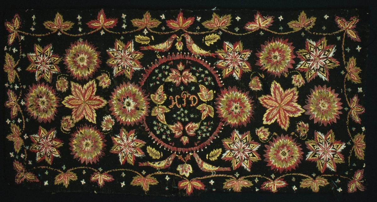 """Dyna i skånskt yllebroderi i rött, grönt, naturvitt och gult ullgarn samt gult, naturvitt och blått löst z-tvinnat bomullsgarn. Bottentyg i ylle i treskaftad kypert: 16 trådar/cm i varp, 10 inslag/cm i s-tvinnat ullgarn. I mitten en cirkel med uddig kant innehållande motställda blad och små stjärnor eller blommor och märkningen """"HPD"""" i stjälksöm och knutar. Parvis fåglar över och under cirkeln. Spridda sex-, åtta- och tjugofyrauddiga stjärnor på var sida om mittcirkeln. Bård runt om. Slinga av blad i rött, grönt, naturvitt och gult ullgarn samt gult, naturvitt och blått bomullsgarn.Baksida av lin-ull vävd i tuskaft (13 trådar/cm, 13 inslag/cm) med ränder av opphämtabårder i gult, rött, grönt och lila ullgarn. Lappad i hörnen. Öppen en bit i ena långsidan. Mer blekt och sliten på baksidan. Dunrester inuti. Dynan från Sjöbo?"""