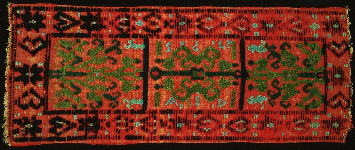 """Åkdyna vävd i halvflossa/trensaflossa. Röd botten i inslagsrips med flossanockor som bildar mönster i två nyanser grönt, blått, turkos-/ljusblått, svart, blårött och gult. Mittspegeln är indelad i tre fält med ett livsträd i varje. I mittfältet är monogrammet och årtalet """"AID 1795"""" invävt. Mellan A:et och I:et är ett """"K"""" broderat i korssöm. Vid de andra två träden finns fåglar. Runt om löper en bård av spetsuddiga stjärnor och hjärtan i svart samt turkos-/ljusblått och gult. Varp i oblekt 2-trådigt s-tvinnat lingarn, 6 trådar/cm (56 trådar/10 cm). Inslag i 1-trådigt z-spunnet ullgarn, ca 24 inslag/cm. Baksida saknas. Kortsidorna är ej fållade, endast kastade med tunt lingarn. MÄrkt med en påsydd tyglapp med texten: """"Landstinget N° 121 a Vemmenhög"""". Intill sitter en vidhängande, trasig pappersetikett tryckt: """"MALMÖHUS LÄNS HEM... MALMÖ"""" .Jämför med: """"Gammal allmogeslöjd från Malmöhus län"""", fig. 414."""
