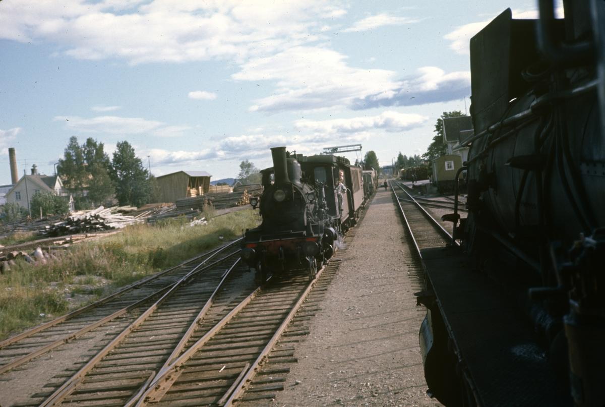 Kryssing mellom to godstog på Kirkenær stasjon på  Solørbanen. Damplok type 27a til venstre og 26c til høyre.
