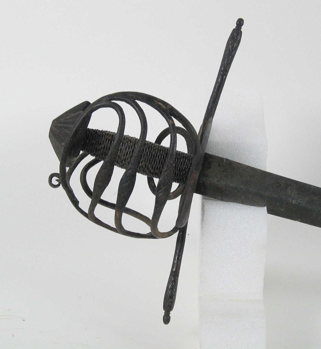 Pyremideformet knapp med strekdekor. Asymmetrisk kurvfeste med tre sidebøyler med riflede fortykkelser på midten mellom håndbøylen og kurvens ytterkant. Innsiden har to sidebøyler. Kurvens basis består av rektangulær parérplater på begge sider. Rette parérstenger med riflede fortykkelser på endene. Tregrep med jerntrådvikling. Enegget svakt krum klinge med bred blodrand ryggslipt mot spissen. Smedmerker på innsiden.