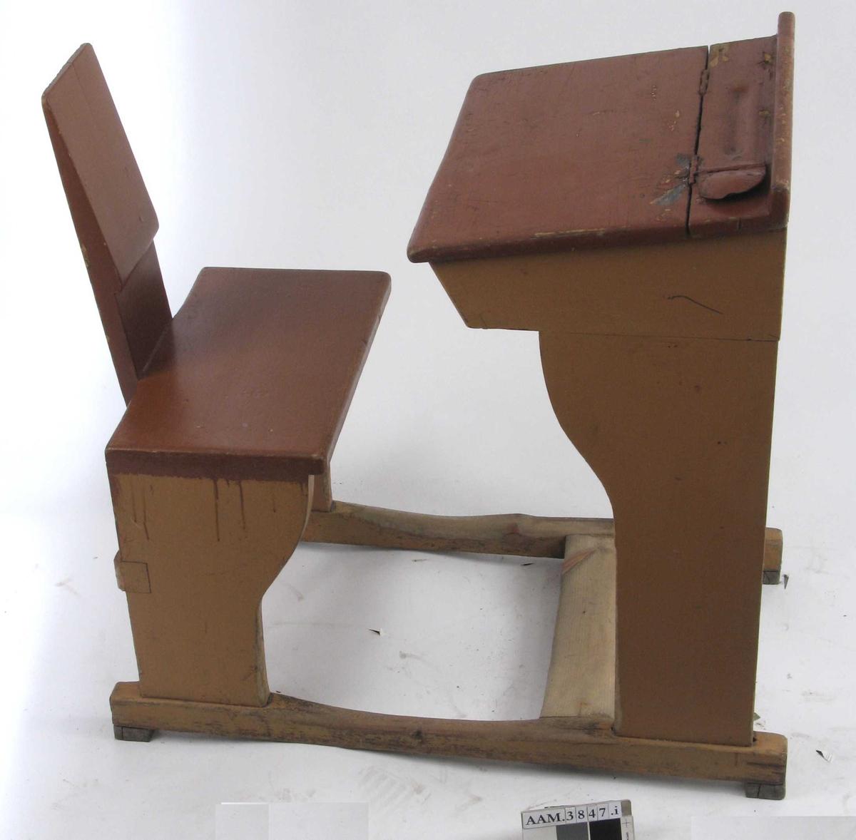 Form: Vanger m. pult og stol i ett. Rom for oppbevaring under plata.  Ådring på sidene. Avflasset på pultlokk. Blåfarget i kasse under lokk. TN har laget malingtrapp på lokket. Viser at pulten er malt 13 ganger.