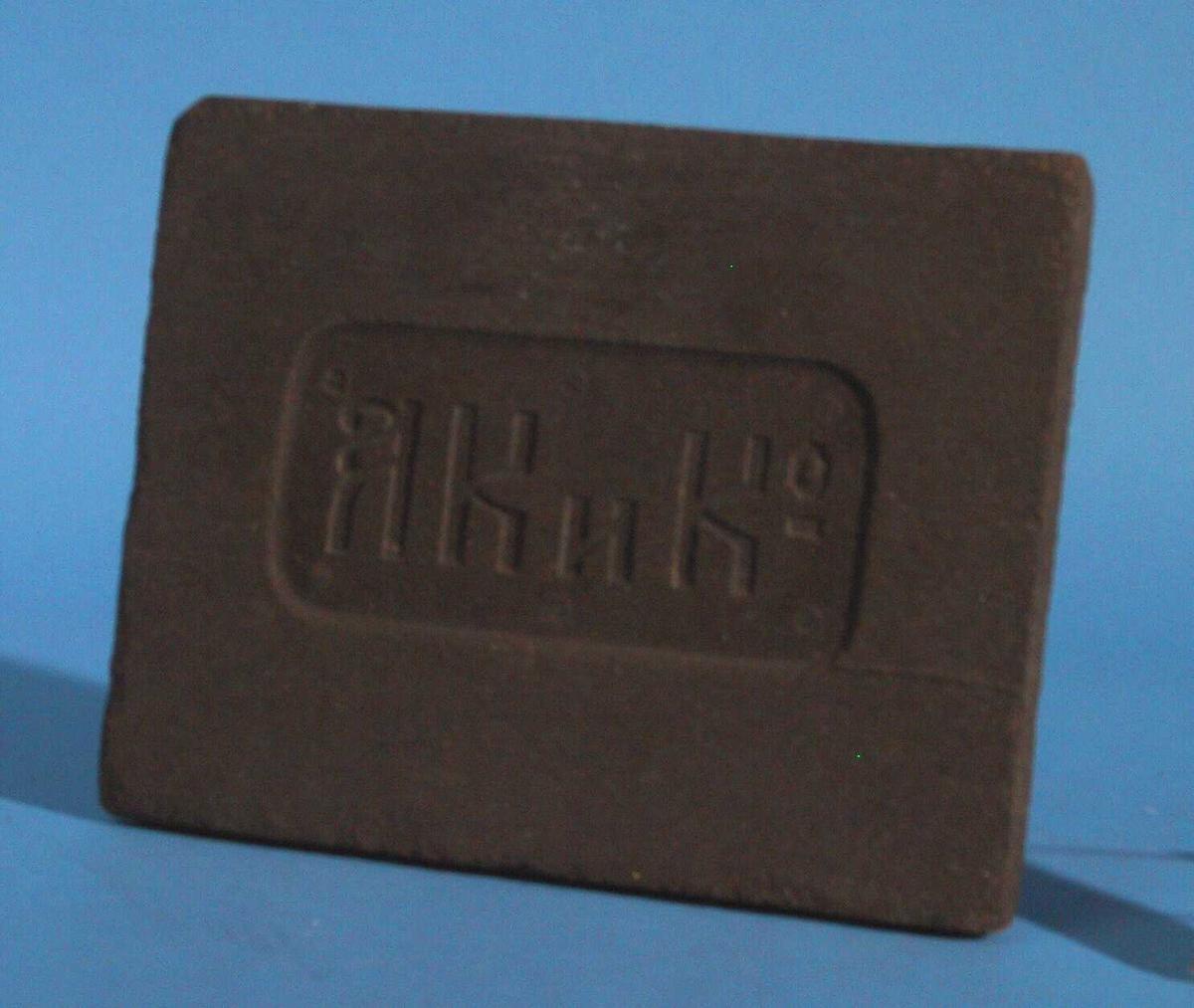 Plate av presset te  fra Kina. På forsiden er et nedsenket felt med fire fem skrifttegn. Platen   trolig brukt som byttemiddel. Mørkebrun av farge. Tilstand sommer 1966 god.