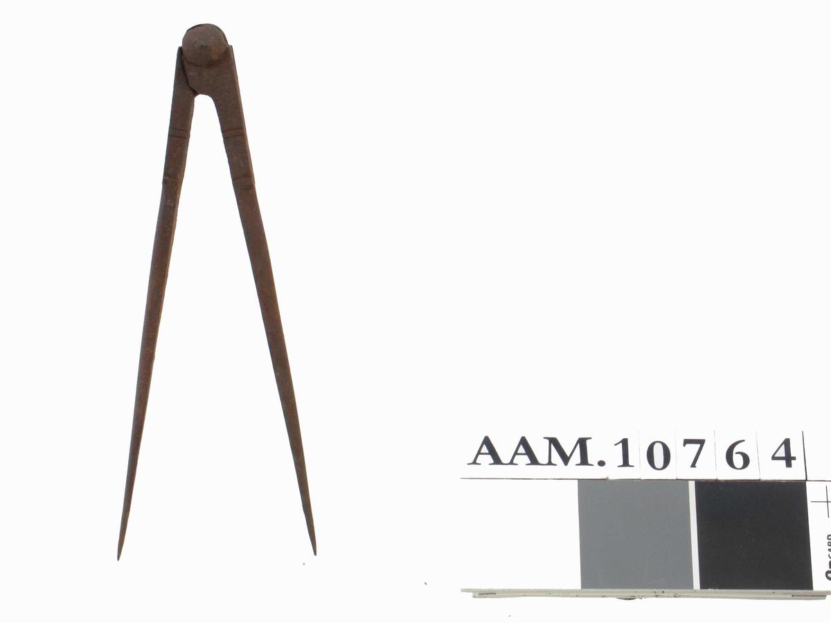 Tømmermannspasser, ca. 1870.1, ustemplet.   L. 20,3.  Sirkelpasser med to like lange armer, kjegleformet  feste øverst og noen tverrgående innskårne linjer  til dekor.  Tilstand: litt rusten, ellers bra.