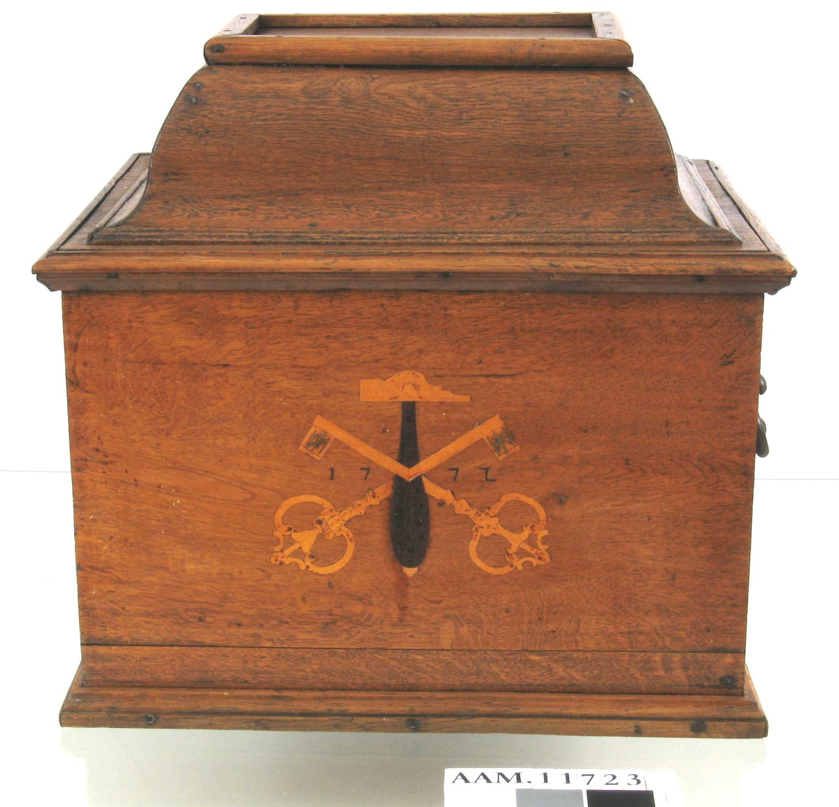 På skrinets forside en hammer med to korslagte nøkler i intarsia og  årstallet 1772.