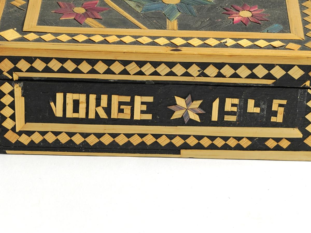 """Skrin med dekor og tekst: Norge 1945.  Tre, trolig osp.  Innvendig hvitmalt, utvendig sort med border i naturfarget bast.  Teksten og blomster i malt bast.  På lokket to blomster og """"1945"""".  På forsiden i blått: """"Norge 1945"""""""