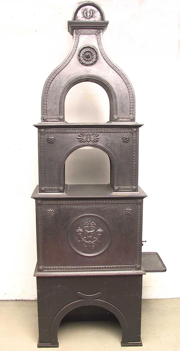 Korslagte overflødighetshorn med Merkurstav i sirkel. Løpende hund-bord  langs overkant og sider, rosett  i øvre hjørner og et ornament  øpm