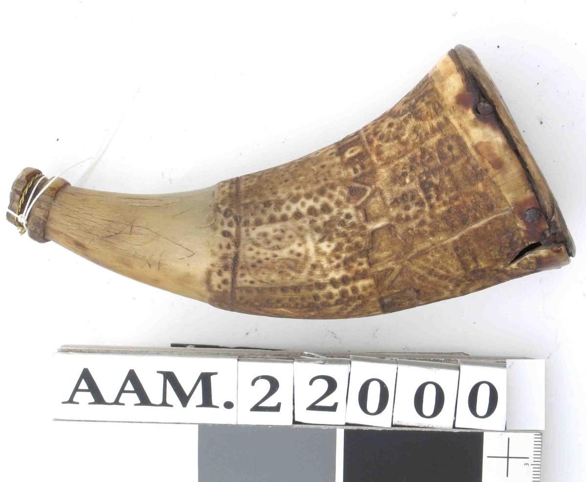 Horn, lyst, med brunere dekorfelt. Avslitt dekorfelt a i øvre 2/3, ornamentale felt. skimter en figur i ett felt. Midt over ornamentfelt et innskriftbånd med opprinneli eiernavn:  Tore Nilson Tved (antagelig Tveit i Lli) 1738.