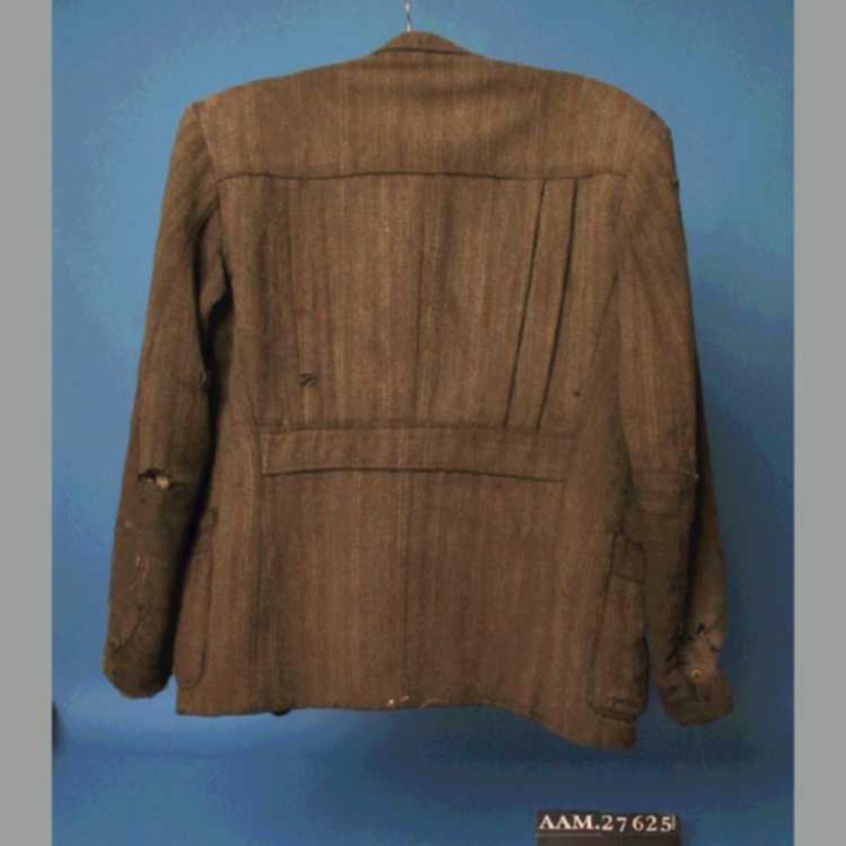 Stipet stoff, krisevare produsert under 2.verdenskrig, blanding av ull og cellull, som ble laget av cellulose. Foret var gammelt - enten noe de hadde liggende, eller sprettet av gamle klær.  Snittet er litt spesielt, trolig for å utnytte små biter stoff.