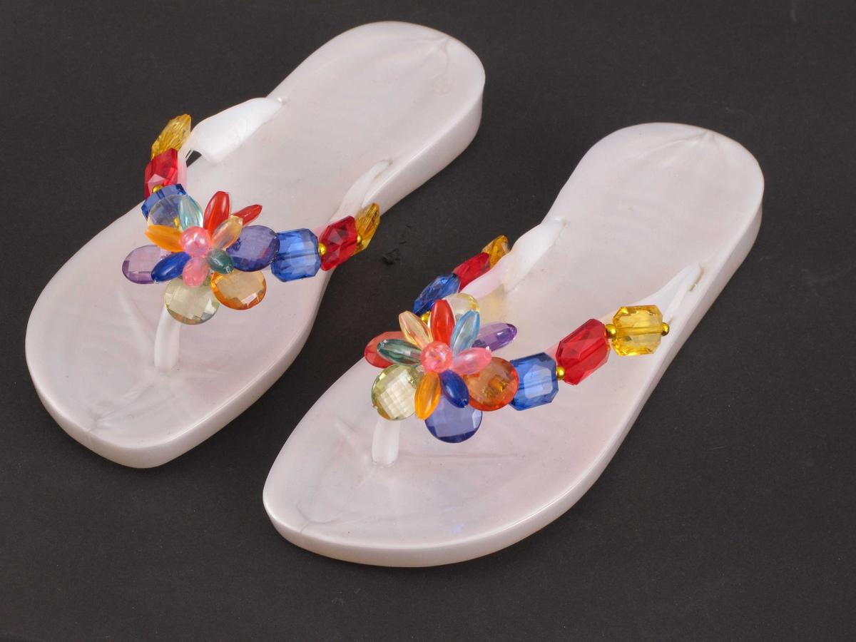 Hvite sandaler i myk, skinnende plast.  Størrelse 32.  Fasong som flipp-flopper med tårem mellom stortå og meste.    På reima over tærne er det festet fargerike firkantede perler med avskårne hjørner i gul, rød og blå plast (bakfra og fremover på hver side) med små runde gullperler mellom.  Midt foran en rosett av seks runde flate perler med hull i kanten ytterst, deretter syv avlange perler innenfor og en rund rosa perle i midten.  De flate perlene er i henholdsvis seks og syv forskjellige farger, men i litt forskjellig rekkefølge og plassering på de to skoene.  Merke: Opta.  Made in Thailand.