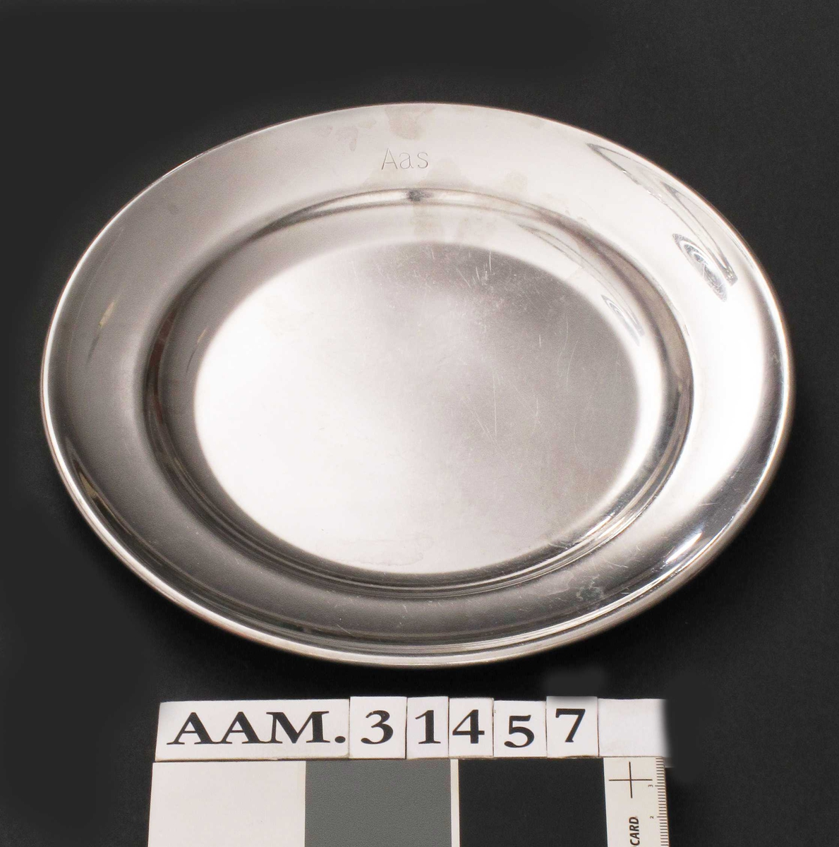 Enkel tallerken i rustfri stål.  Flat bunn, lav side og relativt bred brem som er brettet dobbel langs kanten