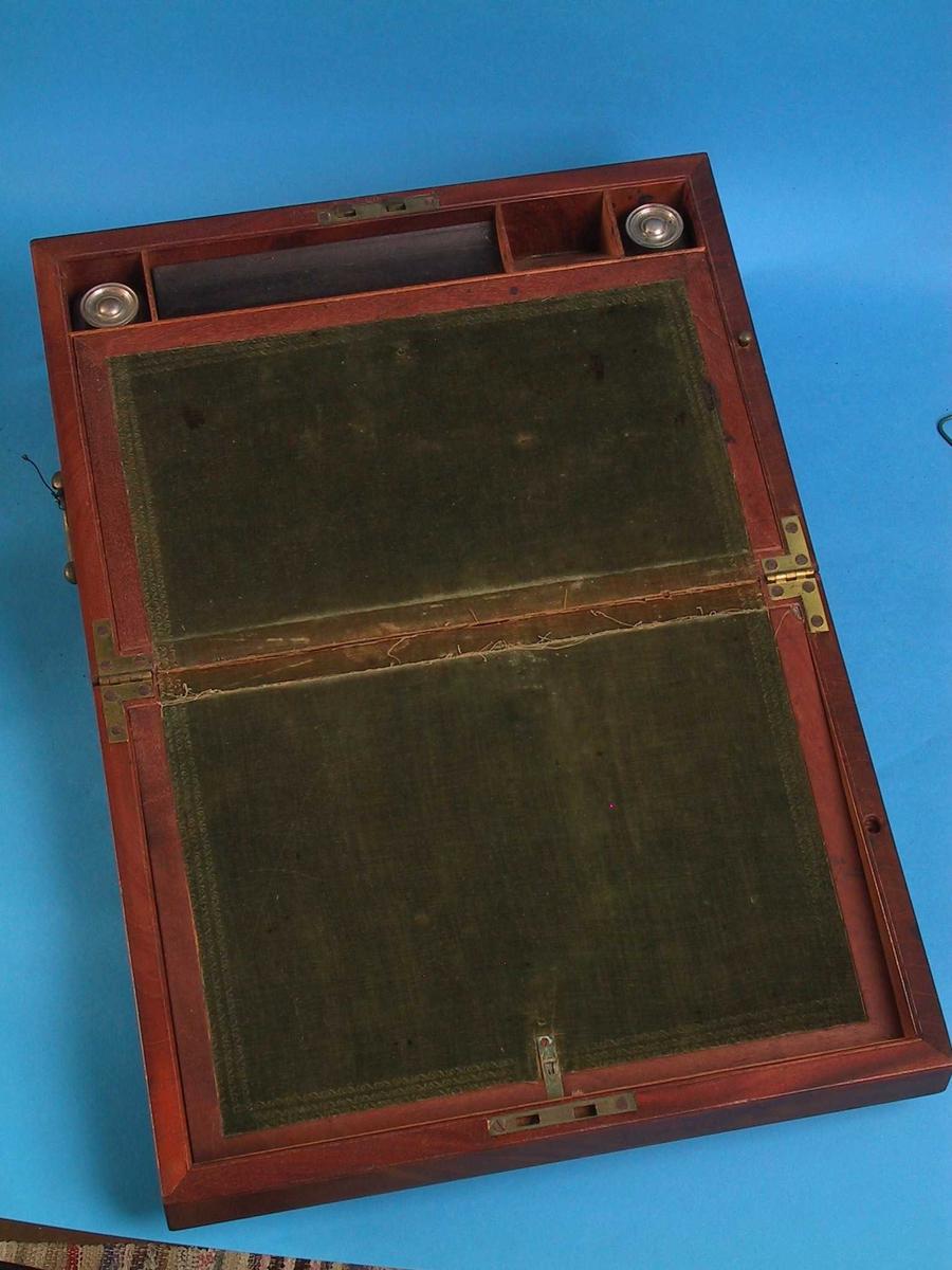 a)  Rektangulært skrin med messing låsbeslag og, en messinghank på hver side. På venstre side  nederst en smal skuff. Oppslått har skrinet  skriveplate med grønn fløyel, som har tre smale innpressede border. I forkant en firkantet lite rom på hver side til blekkhus og sandhus, et lite rom med en skråvegg og et pennerom. b) Blekkhus, glass med kork av jernblikk.  Firkantet flatt blekkhus med størknede rester, rundt 1okk med ringer på toppen. c)  Sandhus, form som blekkhuset (H. 2,8. bunn 3,7x3,7) men med fem dryssehull og innhold blå sand. Gml. nr. AAM.122. Ifgl. Uglands notat på kartotekkortet AMM.122. inneholdt skuffen brev fra 1850-60-årene.