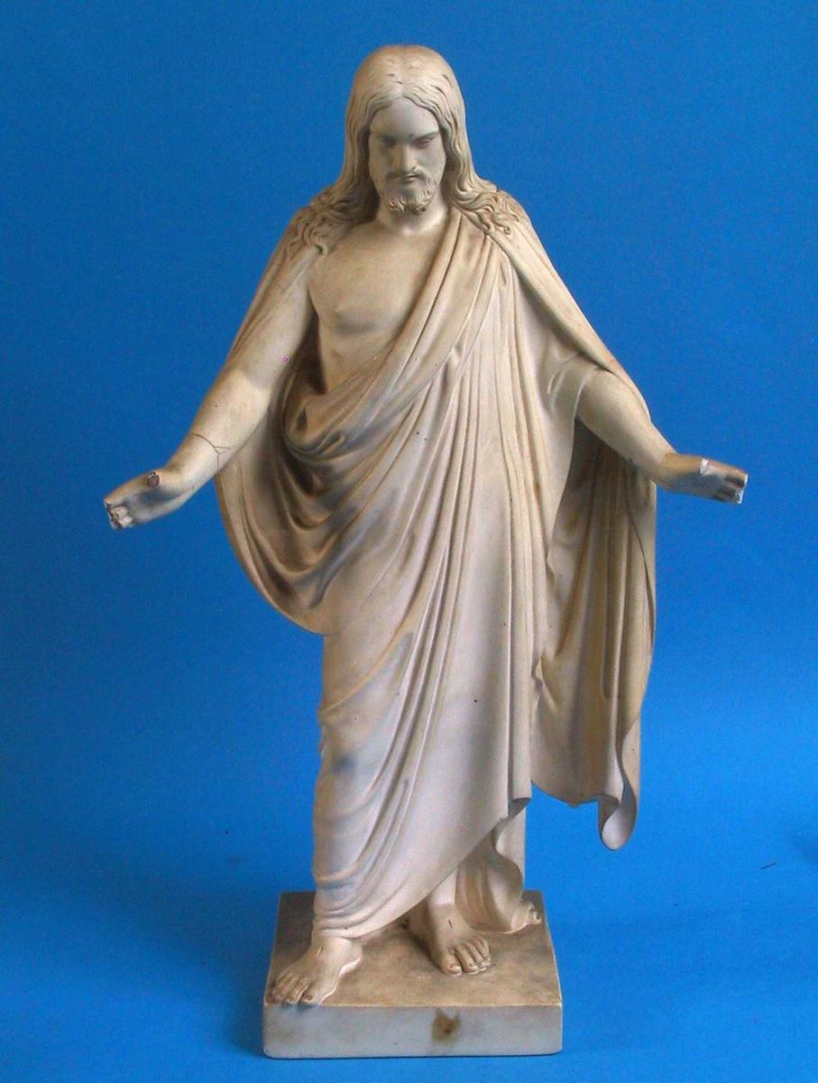 Stående Kristus med armene utstrakt, bøyd hode, kappe over skuldren