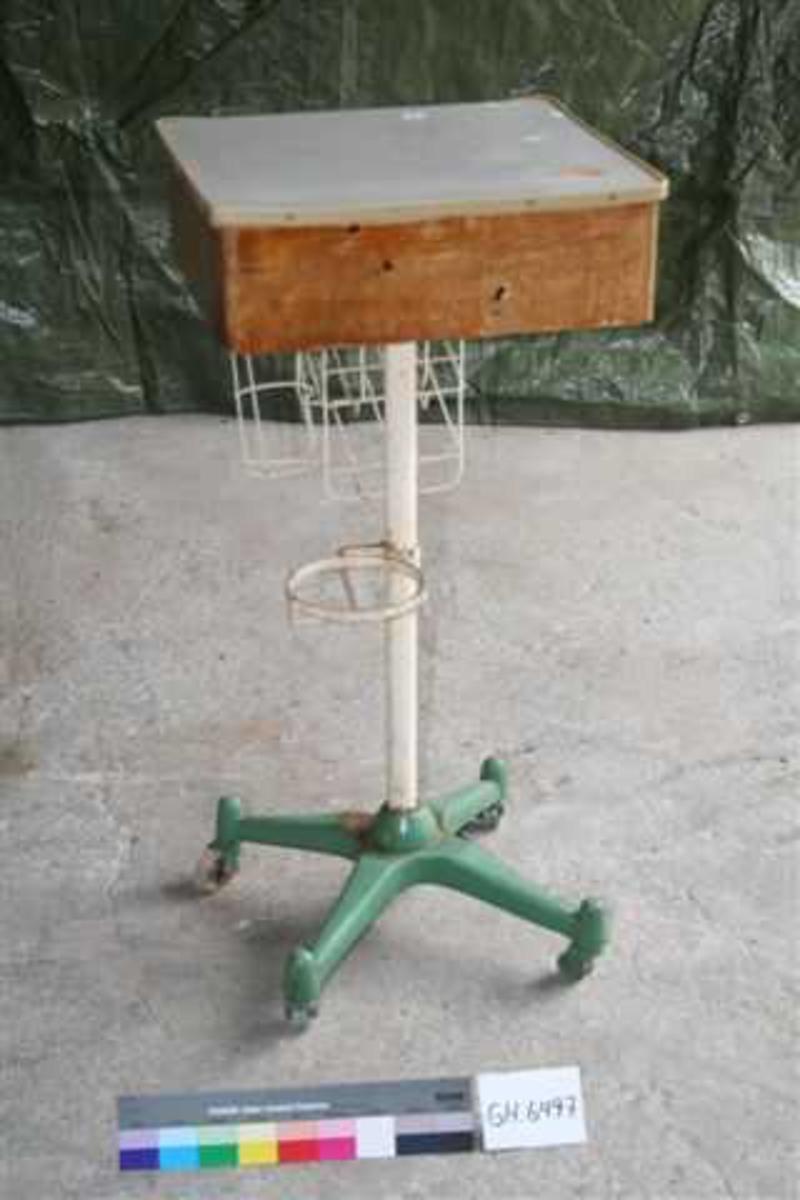 Form: 4-kantet bord med sarg og skuff. Understell av en stang med fire føtter (m.hjul). På stanga er montert holder for en liten bøtte av formpresset blikk, samt kurv.